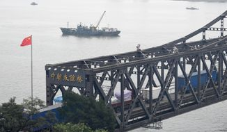 In this Sept. 5, 2017 photo, trucks transport goods to North Korea through the Friendship Bridge linking China and North Korea, as seen from Dandong in northeastern China's Liaoning Province. While condemning North Korea over its latest nuclear test, the leaders of Russia and South Korea seemed far apart on the issue of stepping up sanctions against the country. (Minoru Iwasaki/Kyodo News via AP)