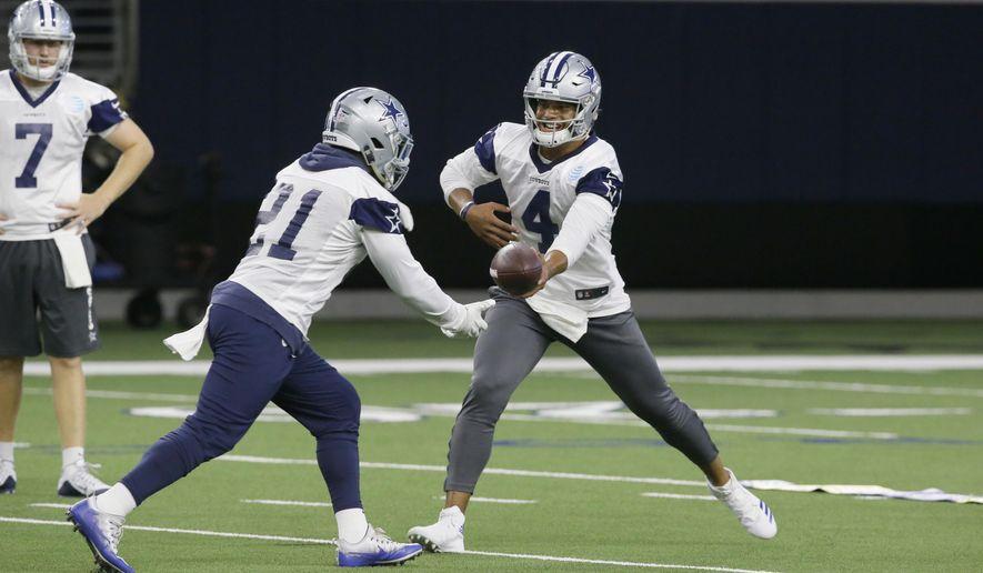 Dallas Cowboys quarterback Dak Prescott (4) hands off to teammate running back Ezekiel Elliott (21) during an NFL football practice in Frisco, Texas, Thursday, Sept. 7, 2017. (AP Photo/LM Otero)