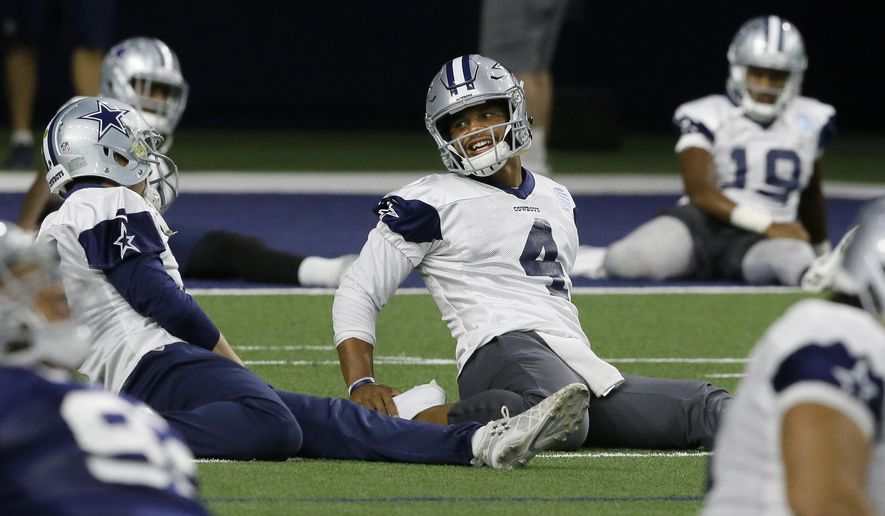 Dallas Cowboys quarterback Dak Prescott (4) talks with a teammate during an NFL football practice in Frisco, Texas, Thursday, Sept. 7, 2017. (AP Photo/LM Otero)