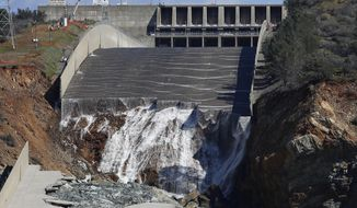 FILE - In this Feb. 28, 2017, file photo, water flows down the Oroville Dam's crippled spillway in Oroville, Calif. A towering spillway at the nation's tallest dam was crumbling and tens of thousands of people were fleeing for their lives, but as darkness fell state managers suddenly discovered the unfolding crisis in Northern California was about to get even worse: They couldn't see. For years federal regulators had urged keepers at the state-run Oroville Dam to install more cameras and other monitors to warn and guide them in just such an emergency. (AP Photo/Rich Pedroncelli, File)