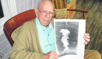 In this Aug. 29, 2017 photo, Donald Williams holds a picture of an atomic bomb going off near Berlin, Pa. Williams remembers when he saw an atomic bomb go off. He was on a ship near Bikini Atoll in the Pacific when the Americans tested it. (Cody McDevitt/Daily American via AP)