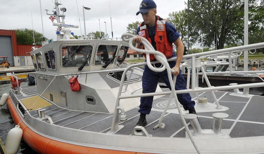 ADVANCE FOR WEEKEND EDITIONS, SEPT. 9-10 - In this Aug. 31, 2017 photo, United States Coast Guard seaman apprentice Tyler Devlin, 21, helps prepare to launch his unit's 45-foot response boat near Erie, PA. (Greg Wohlford/Erie Times-News via AP)