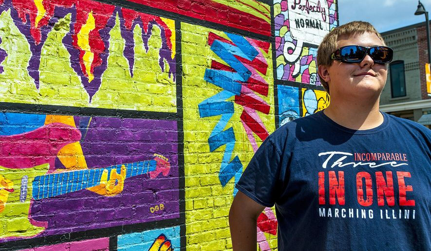 """In this Aug. 10, 2017 photo, Ridgeview High School senior and band member Zach Craig tries out his new Enchroma glasses as he takes in a colorful mural in Normal, Ill. """"I realized I was  colorblind in third grade art class when we were studying the color wheel,"""" said Craig. His best friend and fellow drum major, Justin Givens, has known about Craig's color vision deficiency since seventh grade. When Givens discovered Enchroma glasses, he decided his friend needed a pair. Over the summer, Givens quietly collected $350 in donations from his bandmates with the help of band director Anthony Marchese surprised Craig with the glasses. (Lewis Marien/The Pantagraph via AP)"""