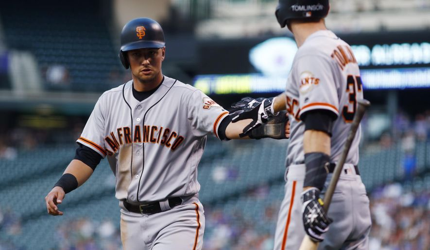 San Francisco Giants' Joe Panik, left, is congratulated by on-deck batter Kelby Tomlinson after Panik and Hunter Pence scored on a single by Austin Slater off Colorado Rockies starting pitcher Kyle Freeland during the first inning of a baseball game Wednesday, Sept. 6, 2017, in Denver. (AP Photo/David Zalubowski)