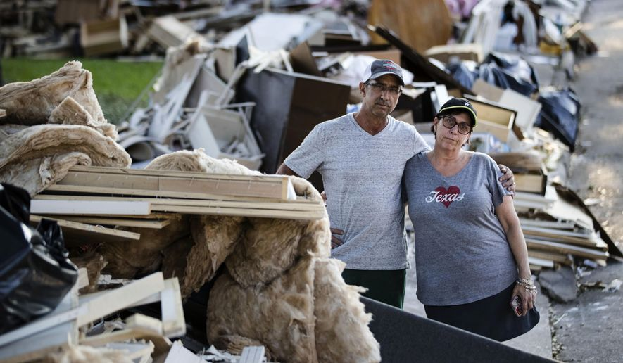 In this Wednesday, Sept. 6, 2017, photo, Steve and Sherri Blatt pose for a photograph amongst the debris from theirs and their neighbors' homes in the aftermath of Hurricane Harvey in Houston. Harvey's record-setting rains now have the potential to set records for the amount of debris one storm can produce. (AP Photo/Matt Rourke)