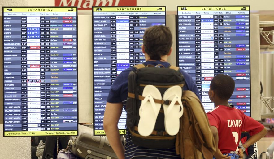 Passengers check the departure board at Miami International Airport Thursday, Sept. 7, 2017. South Florida officials are expanding evacuation orders as Hurricane Irma approaches, telling more than a half-million people to seek safety inland. (AP Photo/Marta Lavandier)