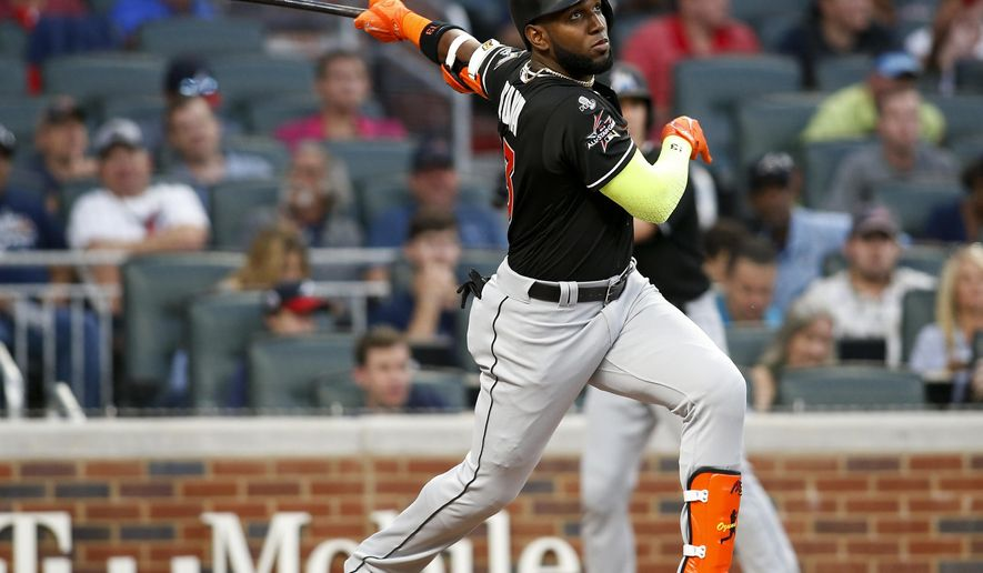 Miami Marlins' Marcell Ozuna watches his RBI triple during the first inning of a baseball game against the Atlanta Braves, Thursday, Sept. 7, 2017, in Atlanta. (AP Photo/Brett Davis)