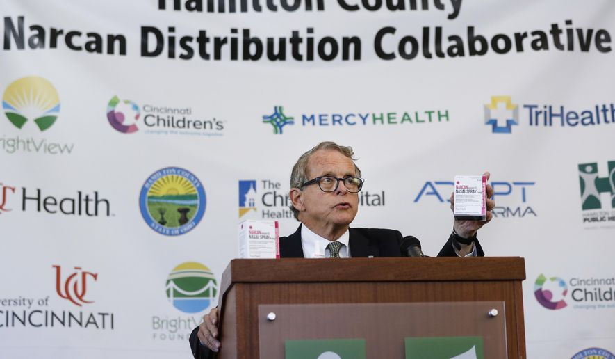 Ohio Attorney General Mike DeWine handles a box of Narcan during a news conference to announce a program and pilot study in Hamilton County to more than quadruple distribution of the opioid overdose-reversing drug to 30,000 units in nasal spray form, Thursday, Sept. 7, 2017, in Cincinnati.  Government and health officials Thursday promoted a plan to dramatically expand availability of the overdose-reversing drug in the southwest Ohio county, in what they hope could prove to be a national model for saving lives.  (AP Photo/John Minchillo)