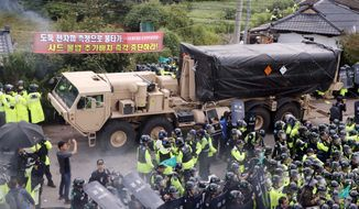 U.S. military vehicle moves as South Korean police officers try to block residents and protesters who oppose to deploy an advanced U.S. missile defense system called Terminal High-Altitude Area Defense, or THAAD, in Seongju, South Korea, Thursday, Sept. 7, 2017. Seoul's Defense Ministry on Thursday said the U.S. military has completed adding more launchers to a contentious U.S. missile-defense system in South Korea to better cope with North Korean threats. The deployment of the Terminal High-Altitude Area Defense system has angered North Korea but also China and Russia, which see the system's powerful radar as a threat to their own security. (Lee Sang-hak/Yonhap via AP)