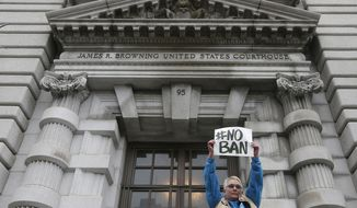 FILE- In this Feb. 7, 2017, file photo, Karen Shore holds up a sign outside of the 9th U.S. Circuit Court of Appeals in San Francisco. The appeals court on Thursday, Sept. 7, rejected the Trump administration's limited view of who is allowed into the United States under the president's travel ban, saying grandparents, cousins and similarly close relations of people in the U.S. should not be prevented from coming to the country. (AP Photo/Jeff Chiu, File)