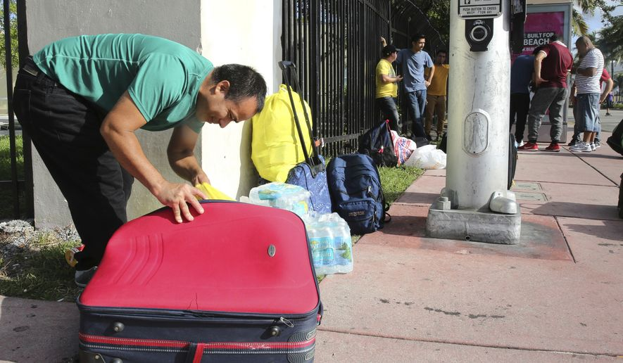 Leonel Geronimo, stuffs food into his suitcase as he and others wait for a bus in anticipation of Hurricane Irma in Miami Beach, Fla., Friday, Sept. 8, 2017. Geronimo wants to get to a shelter off the beach, but is not sure what bus to take or which shelter to go.   (AP Photo/Marta Lavandier)