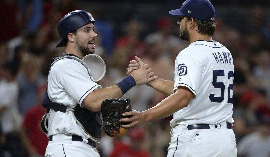 San Diego Padres' Austin Hedges and Brad Hand celebrate after the last out of the team's 3-0 victory over the St. Louis Cardinals in a baseball game Thursday, Sept. 7, 2017, in San Diego. (AP Photo/Orlando Ramirez)