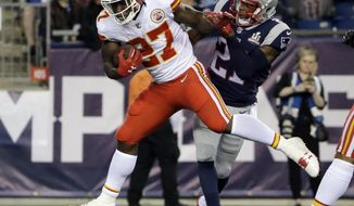 Kansas City Chiefs running back Kareem Hunt (27) eludes New England Patriots cornerback Malcolm Butler (21) as he crosses the goal line for a touchdown after catching a pass from Alex Smith during the second half of an NFL football game, Thursday, Sept. 7, 2017, in Foxborough, Mass. (AP Photo/Steven Senne)