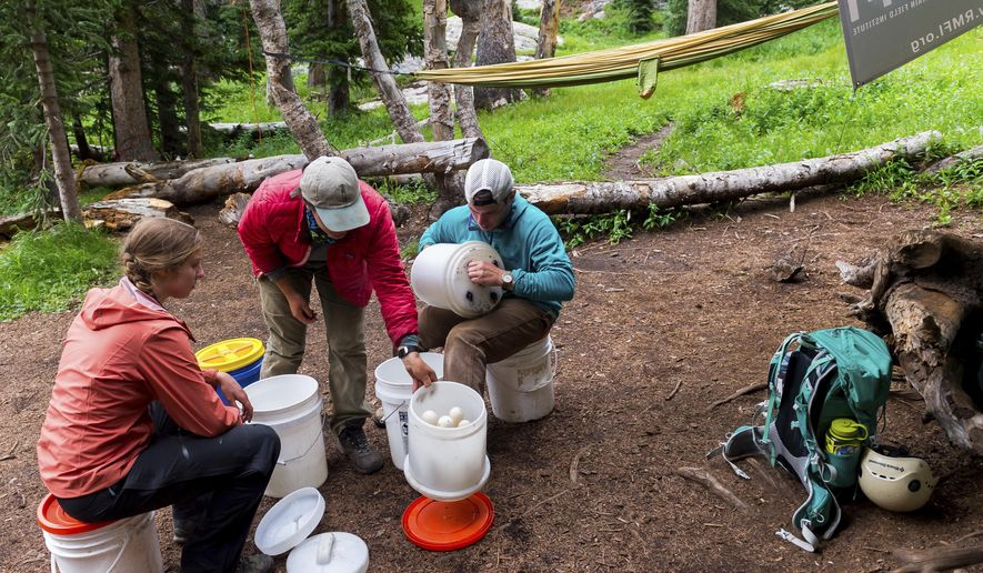 ADVANCE FOR USE SATURDAY, SEPT. 9 - In this July 29, 2017 photo,Mary Lundin, Francesca Watts, Joe Lavorini from left, clean water filters after a day of trail building with the Rocky Mountain Field Institute in Crestone, Colo. If all goes according to plan, the Colorado Springs-based nonprofit will wrap up its arduous effort to build the mile-long reroute to the 14,170-foot summit of Kit Carson Peak by the end of this month. The trail is set to be finished thanks to a compilation of grants and a hearty bunch of 20-somethings from around the country. (Doug Brownlie/The Gazette via AP)