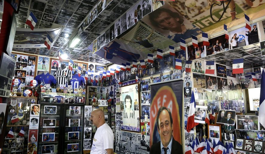 Owner Philippos Stavrou Platini stands by posters and collections of French former soccer great and former UEFA president Michel Platini in his museum at Mosfiloti village on the island of Cyprus, Friday, Sept. 8, 2017. A Cypriot man who idolizes Platini has managed clinched two entries in the latest annual Guinness Book of World Records book for his stash of photos, jerseys, shoes, balls and more centered on him. (AP Photo/Petros Karadjias)