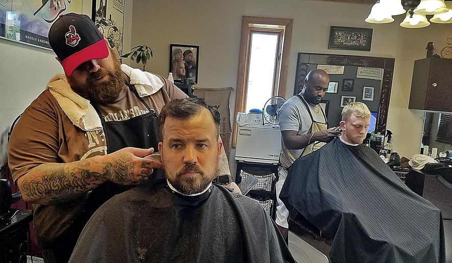 In this Aug. 23, 2017 photo, Johnny Interval, left, owner of the Barbiere, and barber Ed Williams tend to customers Jonathan Gottschall, left, and Trevor Rowland in Washington, Pa. (Scott Beveridge/Observer-Reporter via AP)