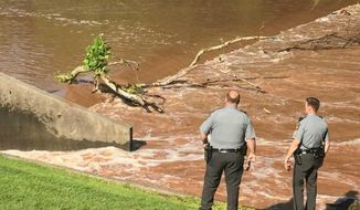 ADVANCE FOR USE SATURDAY, SEPT 9 -  In this July 1, 2017 photo,  Pennsylvania State troopers look at the turbulent water of a low head dam in Swatara Creek in Lebanon, Pa., where Perry Ratcliffe Jr. died while kayaking. Based on toxicology reports, alcohol and drug use were not factors in the 36-year-old's death. However, according to state troopers who investigated his drowning, he was not wearing a life jacket, which may have saved his life. (John Latimer/Lebanon Daily News via AP)