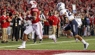 FILE - In this Sept. 1, 2017, file photo, Wisconsin running back Jonathan Taylor, left, scores a touchdown against Utah State's Gaje Ferguson during an NCAA college football game in Madison, Wis. Starting running back Bradrick Shaw is questionable for the game with Florida Atlantic, with a right leg injury, though Wisconsin still has plenty of options. Freshman Taylor had a terrific debut last week with 87 yards on nine carries. Chris James, a transfer from Pittsburgh, is eager is to get over a slow start after playing in his first game since the 2015 season. (AP Photo/Andy Manis, File)