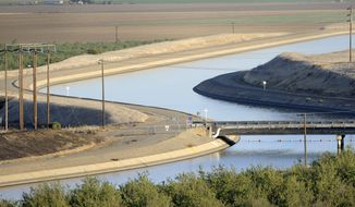 FILE- In this Oct. 2, 2009 file photo, in California's Westland Water District of the Central Valley, canals carry water to southern California. A new federal audit says the federal government improperly spent tens of millions of dollars on the California water project. An audit by the inspector general's office of the U.S. Interior Department says federal officials contributed the taxpayer money to Gov. Jerry Brown's plans to build two giant water tunnels. (AP Photo/Russel A. Daniels, File)