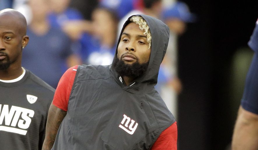 In this Aug. 31, 2017, file photo, New York Giants wide receiver Odell Beckham watches his teammates warm up before an NFL preseason football game against the New England Patriots, in Foxborough, Mass. Beckham Jr. has been listed as questionable for the Giants' season opener against the Cowboys in Dallas on Sunday night. Questionable in NFL terminology is a 50-50 chance to play.(AP Photo/Steven Senne, File)
