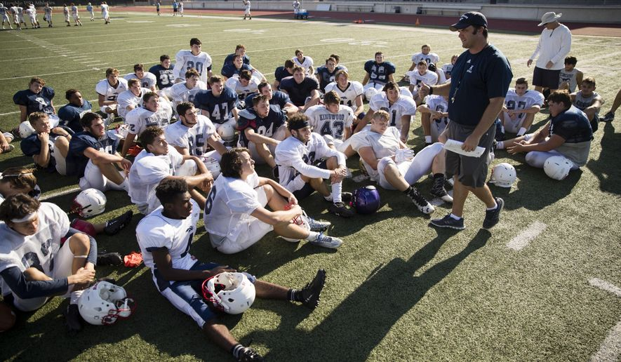 Coach Barry Campbell speaks with the Kingwood High School football team at the end of practice Thursday, Sept. 7, 2017, at Turner Stadium in Humble, Texas. Damage from Hurricane Harvey to their school forced the Kingwood team to practice 9 miles away at another high school and its students will attend classes at still another school in the days to come. (AP Photo/Matt Rourke)