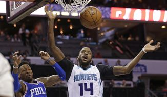 FILE - In this Feb. 13, 2017, file photo, Charlotte Hornets' Michael Kidd-Gilchrist (14) dunks past Philadelphia 76ers' Robert Covington (33) in the first half of an NBA basketball game in Charlotte, N.C. Hornets coach Steve Clifford emphatically threw his support behind Kidd-Gilchrist, saying the often criticized small forward is a key member of the team and will continue to start. (AP Photo/Chuck Burton)