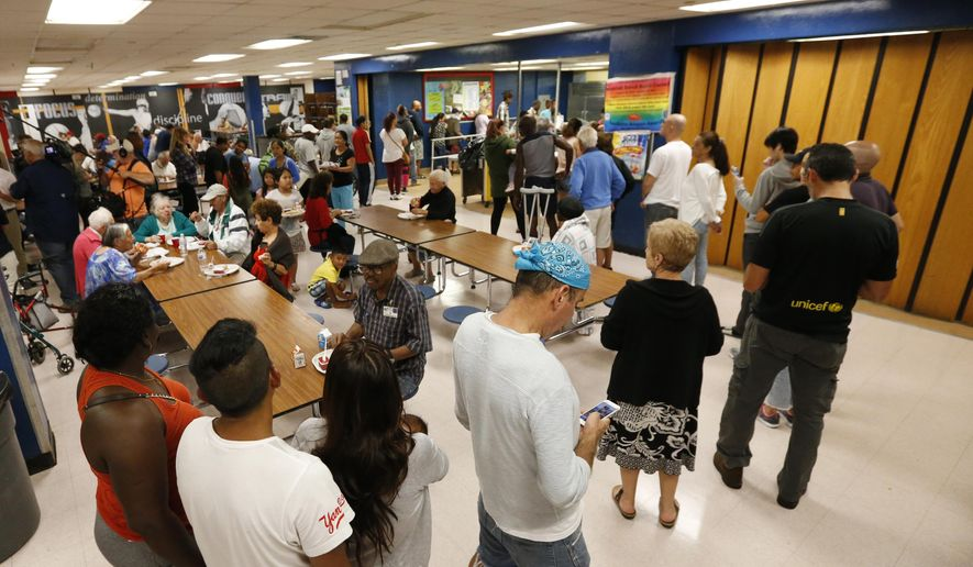 People at a Red Cross shelter set up at North Miami Beach Senior High School wait in line for lunch, Friday, Sept. 8, 2017 in North Miami Beach, Fla. Cuba evacuated tourists from beachside resorts and Floridians emptied stores of plywood and bottled water after Hurricane Irma left at least 20 people dead and thousands homeless on a devastated string of Caribbean islands and spun toward Florida for what could be a catastrophic blow this weekend. (AP Photo/Wilfredo Lee)