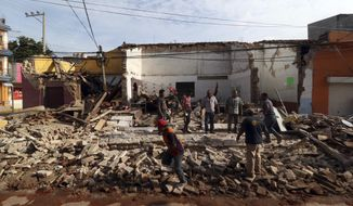 Residents stand on debris of a partially collapsed building felled by a massive earthquake in Juchitan, Oaxaca state, Mexico, Friday, Sept. 8, 2017. One of the most powerful earthquakes ever to strike Mexico has hit off its southern Pacific coast, killing at least 32 people, toppling houses, government offices and businesses. (AP Photo/Luis Alberto Cruz)