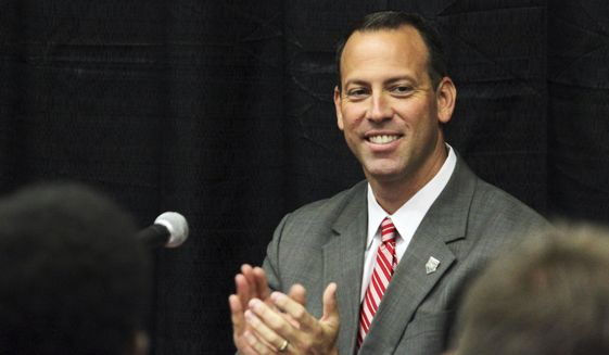 New Mexico athletic director Eddie Nunez claps as members of the selection committee that chose him as a finalist for the job stand during a news conference in Albuquerque, N.M., Friday, Sept. 8, 2017. Nunez said financial responsibility, integrity and transparency will be expected at every level within the athletics department moving forward. (AP Photo/Susan Montoya Bryan)