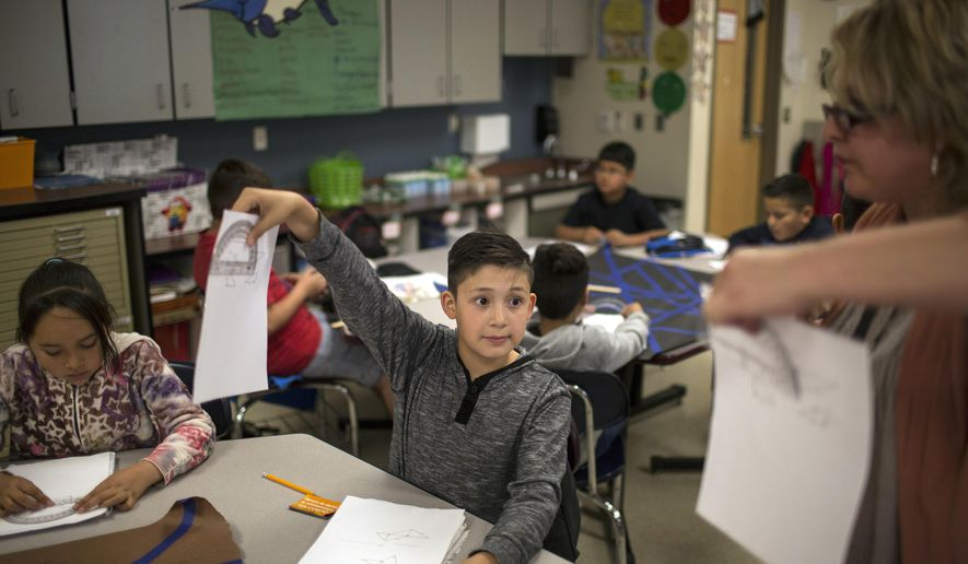 FILE - In this March 31, 2017, file photo, a fifth grade student shows his geometry work to a teacher at Columbus Elementary School in Columbus, New Mexico. New Mexico public education officials released the results of the latest round of teacher evaluations, Friday, Spet. 7, 2017. Officials say around 74 percent of public school teachers in New Mexico are effective or better when it comes to their success in the classroom. (AP Photo/Rodrigo Abd, File)