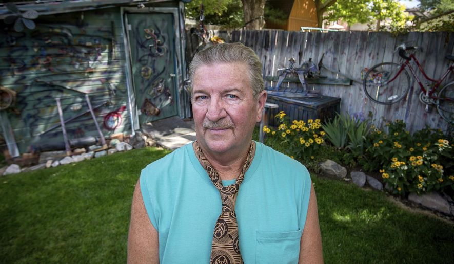 "In this Aug. 23, 2017 photo, Rex Hipwell stands surrounded by some of the ""gutter art"" that lines the fences around his Roy, Utah home. Hipwell makes the recycled artwork out of scraps of materials that he finds around town. His wife eventually gave his painted collages the name ""gutter art.""  (Benjamin Zack/Standard-Examiner via AP)"