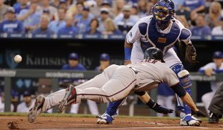 Minnesota Twins' Brian Dozier beats the tag at home by Kansas City Royals catcher Salvador Perez to score on a sacrifice fly by Eddie Rosario during the first inning of a baseball game Friday, Sept. 8, 2017, in Kansas City, Mo. (AP Photo/Charlie Riedel)