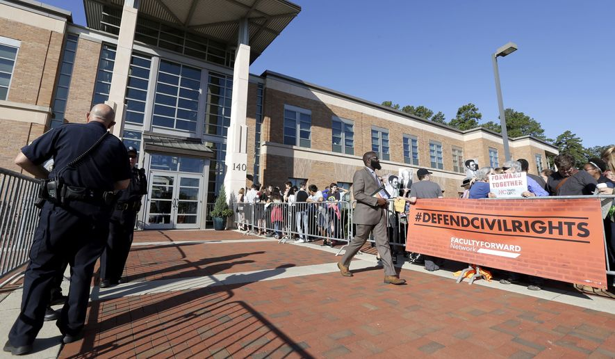 Protesters gather outside while police stand by during the UNC Board of Governors meeting in Chapel Hill, N.C., Friday, Sept. 8, 2017. The policymaking board of the UNC system voted overwhelmingly Friday to ban litigation by the UNC Center for Civil Rights, which handles issues such as school desegregation and environmental justice. (AP Photo/Gerry Broome)