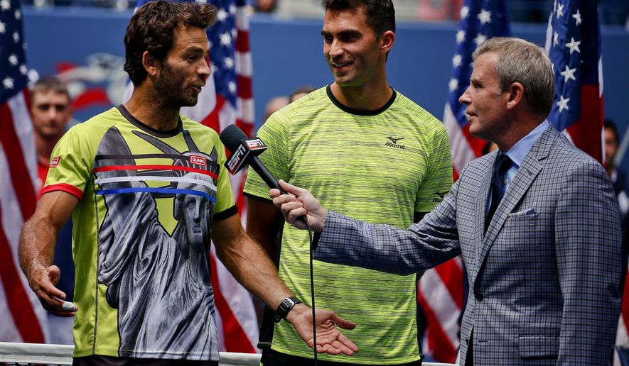 Dutch tennis player Jean-Julien Rojer, left, talks with ESPN reporter Tom Rinaldi as doubles partner Horia Tech, of Romania, listens, after the two won the doubles championship match against Marc Lopez, and Feliciano Lopez, of Spain after the doubles championship match of the U.S. Open tennis tournament, Friday, Sept. 8, 2017, in New York. Rojer wore a shirt showing the Statue of Liberty while winning the U.S. Open men's doubles championship on Friday to send what he called a message about peace and freedom in the aftermath of last month's violence at a rally of neo-Nazis and white nationalists in Charlottseville, Virginia. (AP Photo/Julie Jacobson)