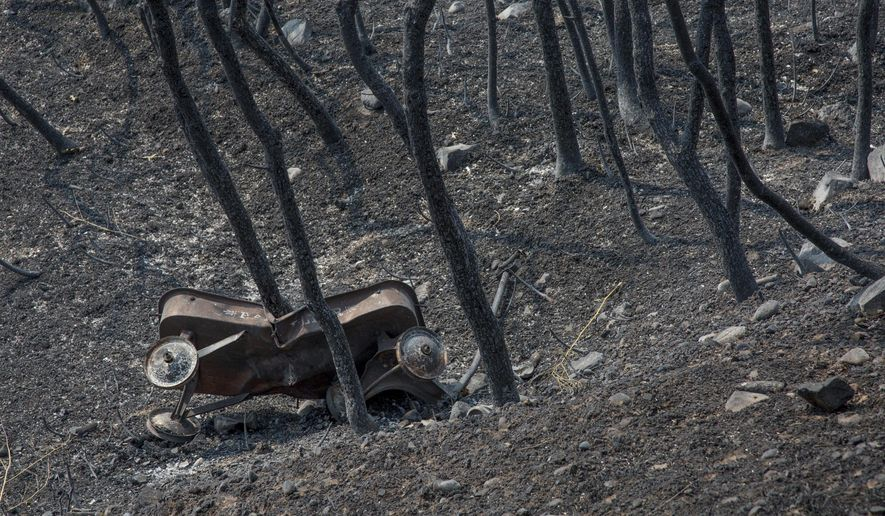 A toy wagon leans against dead brush off of Bybee Dr. in Weber County in the aftermath of the Uintah Fire on Wednesday, Sept. 6, 2017. Most of the homes along Bybee were undamaged in the fire, but several houses were destroyed. (Benjamin Zack/Standard-Examiner via AP)