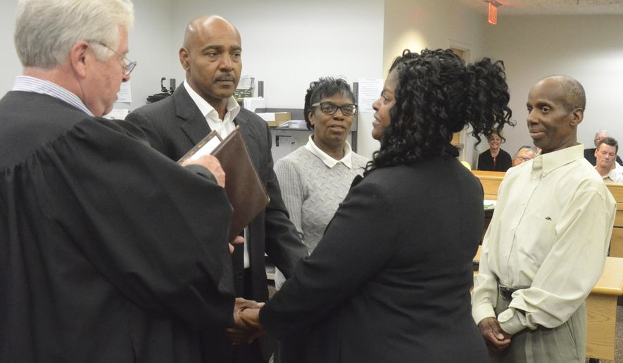 In this Thursday, Sept. 7, 2017 photo, Calhoun County District Court Judge Frank Line, left, presides over the wedding of Sherry Roney and Peter Moore after a session of Calhoun County Veterans Treatment Court in Battle Creek, Mich. The witnesses in the background are Sherry Roney's siblings, Frederick Roney and Kim Wiklie. Moore is a longtime veteran who was enrolled in the treatment program after an arrest for larceny. He now mentors other veterans. He says the court's judge and veterans have become his family. (Trace Christenson/Battle Creek Enquirer via AP)
