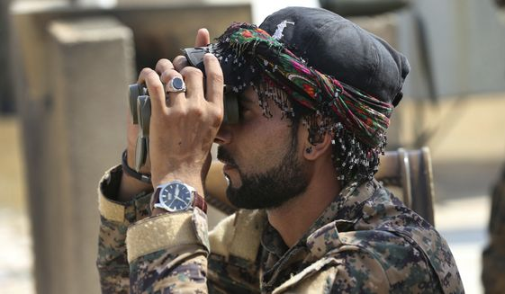 """An Arab fighter with U.S.-backed Syrian Democratic Forces keeps watch during coalition airstrikes against Islamic State. With Syrian government forces besieging Raqqa on another front, an SDF military commander this week told The Associated Press that the fight to retake the Islamic State stronghold was """"in its final stages."""" (Associated Press/File)"""
