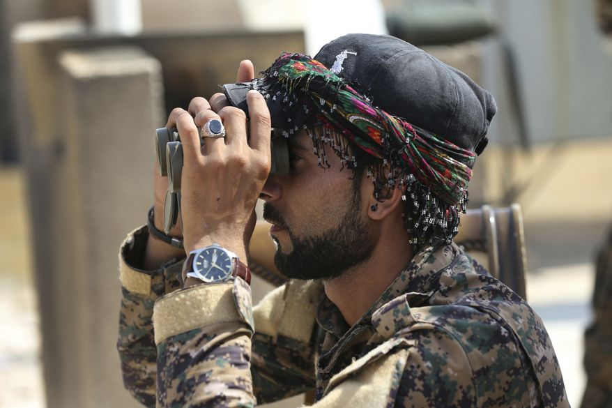 "An Arab fighter with U.S.-backed Syrian Democratic Forces keeps watch during coalition airstrikes against Islamic State. With Syrian government forces besieging Raqqa on another front, an SDF military commander this week told The Associated Press that the fight to retake the Islamic State stronghold was ""in its final stages."" (Associated Press/File)"