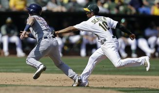Houston Astros' Alex Bregman, left, is tagged out in a rundown between second and third base by Oakland Athletics' Marcus Semien (10) in the fifth inning of the first baseball game of a doubleheader on Saturday, Sept. 9, 2017, in Oakland, Calif. (AP Photo/Ben Margot)