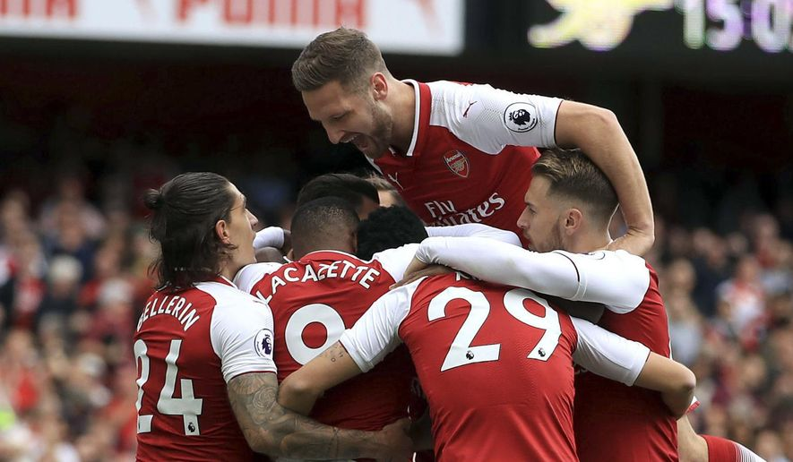 Arsenal's Danny Welbeck is surrounded by teammates as they celebrate him scoring his side's first goal of the game, during the English Premier League soccer match between Arsenal and Bournemouth, at the Emirates Stadium, in London, Saturday Sept. 9, 2017. (John Walton/PA via AP)