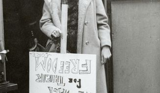 """In this March 12, 1961 photo, an unidentified protester carries a sign that reads: """"Woolworth's Customer's JAILED. We walk for their Freedom"""" during a Lunch Counter demonstration at Woolworth's on Canal Street in New Orleans, organized by The Congress of Racial Equality.  Sit-ins and protests in the 1960s at businesses along Canal Street are among areas the Historic New Orleans Collection plans to interview civil rights leaders and activists about for a new oral history project underwritten with a $23,000 National Park Service grant. The oral histories will discuss the civil rights movement in New Orleans from the 1950 into the 1970s.  (Charles H. Bennett/NOLA.com The Times-Picayune via AP)"""