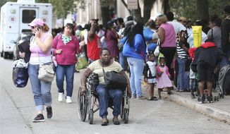 Michelle Wright, 50, arrives in her wheelchair joining hundreds of local residents being evacuated from the city at the Savannah Civic Center during a mandatory evacuation from Hurricane Irma on Saturday, Sept. 9, 2017, in Savannah, Ga.  (Curtis Compton/Atlanta Journal-Constitution via AP)