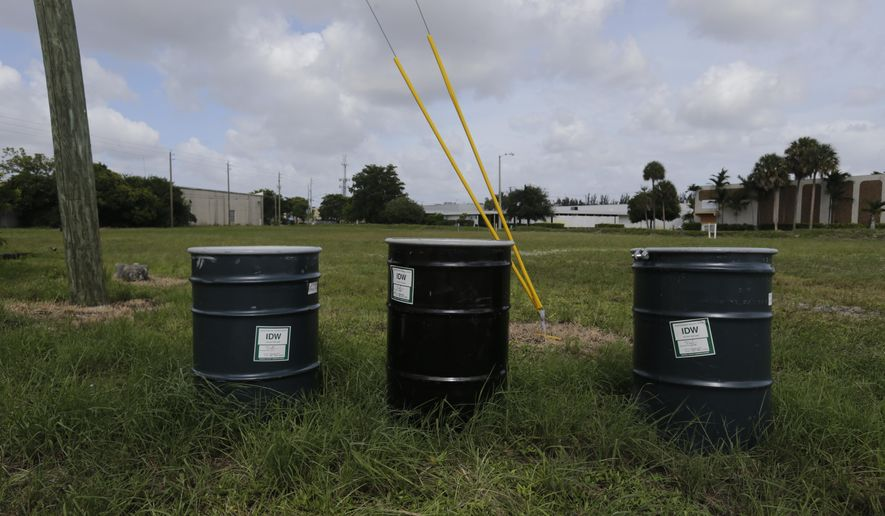 """Barrels identified by stickers as IDW, or """"investigation derived waste,"""" full of soil and water sit in a field designated by the EPA as an intensely polluted Superfund site called Anodyne North Miami Beach on Sept. 6, 2017.  At least five of the most flood-prone Superfund sites located in South Florida are in various stages of cleanup. Strong winds and driving rains from Irma could damage years of cleanup work completed at the sites and spread contamination, endangering public health by spreading the contamination. contamination. EPA spokeswoman Liz Bowman said the barrels were low-risk to human health and said an EPA contractor will remove them before Hurricane Irma hits Florida. (AP Photo/ Jason Dearen)"""