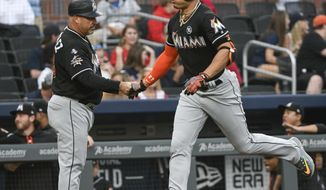 Miami Marlins' Giancarlo Stanton rounds third base and shakes hands with third base coach Fredi Gonzalez, left, on a home run to centerfield against the Atlanta Braves during the first inning of a baseball game, Saturday, Sept. 9, 2017, in Atlanta. (AP Photo/John Amis)
