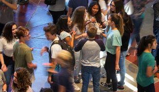 In this Aug. 31, 2017 photo, high schoolers gather at the school for ice cream and were able to talk to teachers and staff incoming freshmen during a welcome night assembly at West Seattle High School before classes officially start Sept. 6, in Seattle. In Seattle, city officials are focusing freshman-support efforts at five high schools, Cleveland, Franklin, Ingraham, Interagency Academy and West Seattle. (Ellen M. Banner/The Seattle Times via AP)