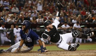 Arizona Diamondbacks' Chris Herrmann, right, shows the umpire the ball in his glove after tagging out San Diego Padres' Manuel Margot, left, as Margot tried to score during the third inning of a baseball game Friday, Sept. 8, 2017, in Phoenix. (AP Photo/Ross D. Franklin)
