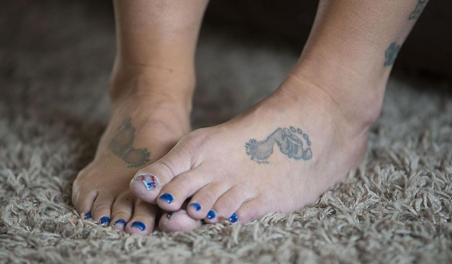 In this Aug. 29, 2017, photo, The footprints of sons Justin and Tristan when they were infants are seen tattooed to the feet of Heather Fuller at her home in La Center, Wash. (Amanda Cowan/The Columbian via AP)