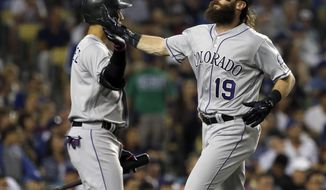Colorado Rockies' Charlie Blackmon, right, celebrates with Carlos Gonzalez after scoring on a double by DJ LeMahieu during the fifth inning of a baseball game against the Los Angeles Dodgers in Los Angeles, Friday, Sept. 8, 2017. (AP Photo/Alex Gallardo)
