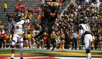 Maryland wide receiver D.J. Moore, center right, celebrates his touchdown with teammate Jacquille Veii in front of Towson defensive back Monty Fenner, left, and cornerback Justice Pettus-Dixon, right, in the first half of an NCAA college football game in College Park, Md., Saturday, Sept. 9, 2017. (AP Photo/Patrick Semansky)