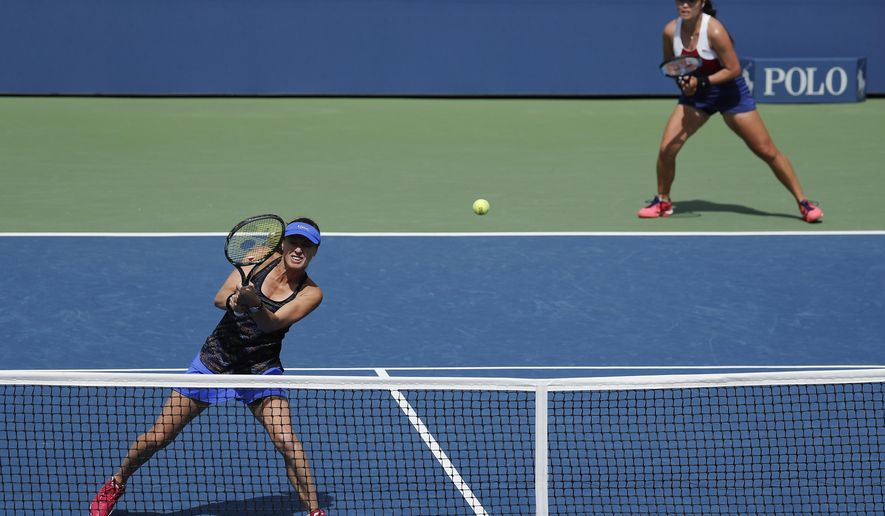 Martina Hingis, of Switzerland, left, returns a shot as doubles partner Chan Yung-Jan, of Taiwan, looks on during the doubles semifinals of the U.S. Open tennis tournament against Sania Mirza, of India, and Peng Shuai, of China, Friday, Sept. 8, 2017, in New York. (AP Photo/Julie Jacobson)